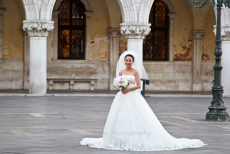 Bride posing for wedding photos early in the morning at Piazza San Marco or St. Mark's Square, Venice, Italy