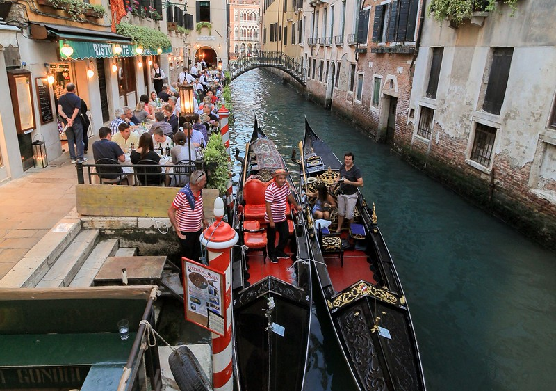 Venice docking station. Gondolas, by law, are made of light wood to reduce wake and impacts on vulnerable docks and foundations.