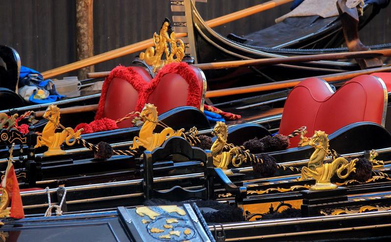 Some gondola handrails sport ornate, golden horse brackets.