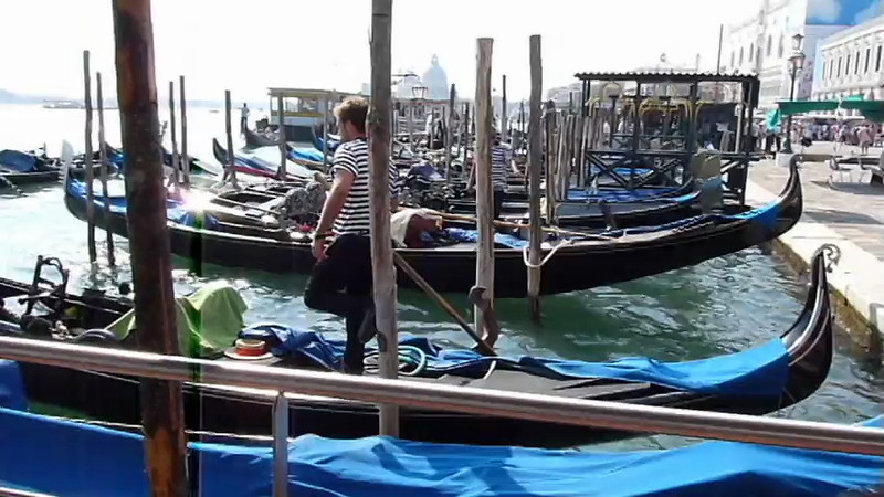 Gondolas and boats docked along the canal in Venice, Italy.
