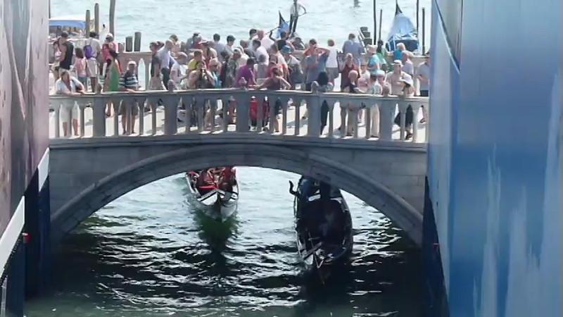 Gondola boat cruises under the bridge in Venice, Italy.