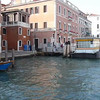 A water bus approaches the dock station along the canal in Venice, Italy.