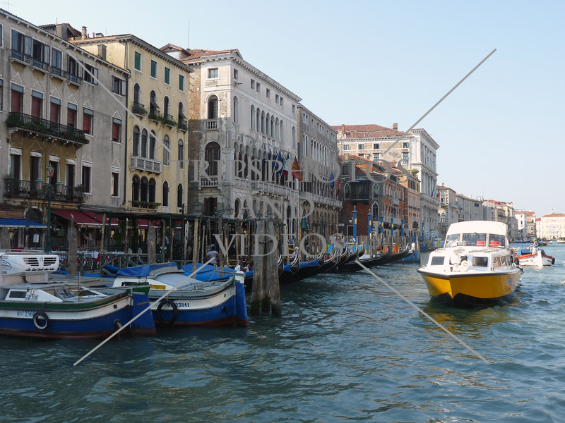 Water taxi cruising along the Grand Canal past the Gondolas and boats in Venice, Italy.