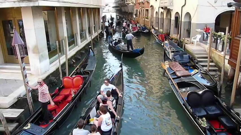 Gondoliers maneuver the gondolas along the canal in Venice, Italy.