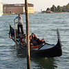 Gondolier maneuvers the gondola along the canal in Venice, Italy.
