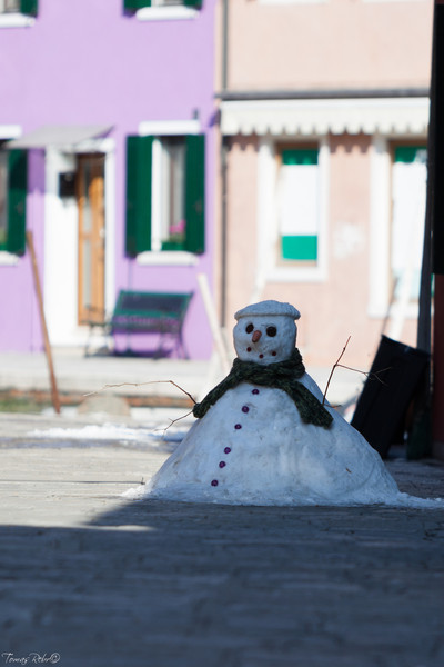 Snowman hidden in shadow on colorful street of island Burano