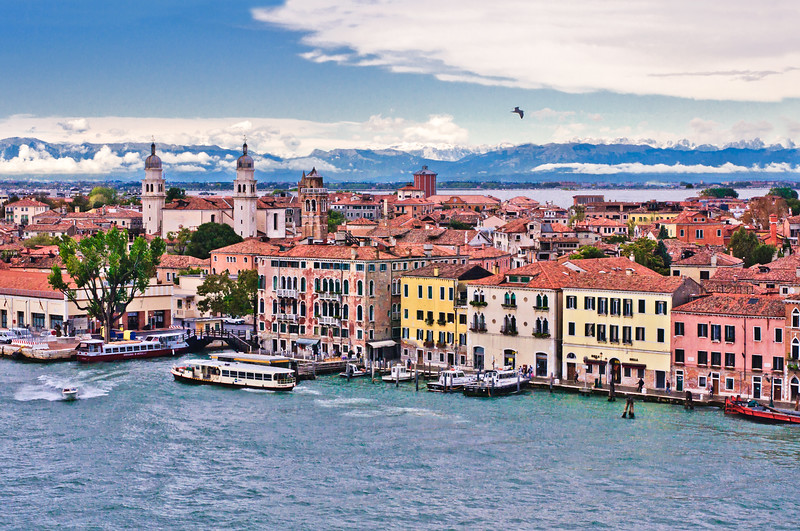 Venice, Italy - Toward the end of the Dorsoduro district and the Giudecca Canal.  The building on the far left is the beginning of the port area where cruise ships dock.  The two bell towers with rounded tops mark the Church of the Angel San Rafael, from the early 17th century.  The brick bell tower belongs to the Church of St Sebastiano, which was built in the mid 15th century.