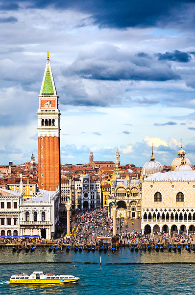Venice, Italy - A closeup of the entrance to St Mark's Square, looking down from the top deck of a cruise ship, showing all components of the square.  On the far left is the Nazaionale Biblioteka Marciana (National Library), with the Bell Tower behind it.  Toward the back is the white and blue Clocktower leading into Venice. Directly to the right is St Mark's Basilica and the Ducal Palace.