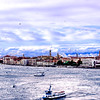 Venice, Italy - Leaving Venice after a rainy cold front moved through.  The entrance to the Grand Canal with the Bell Tower of Saint Mark's Square on the far right and the foothills of the Alps in the background.