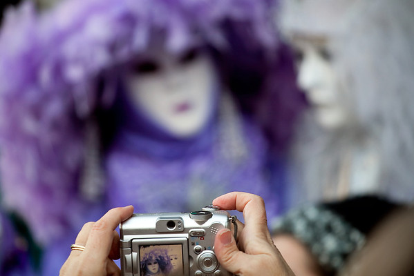 Taking a picture of masks on carnival, Piazza San Marco, Venice, Italy