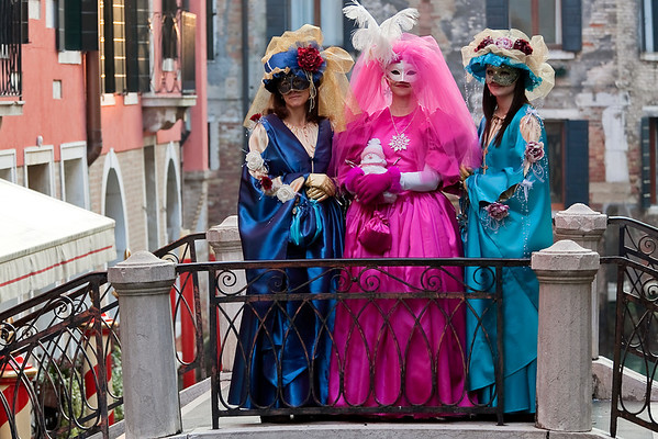 Three women in masks posing for photographers, Venice, Italy