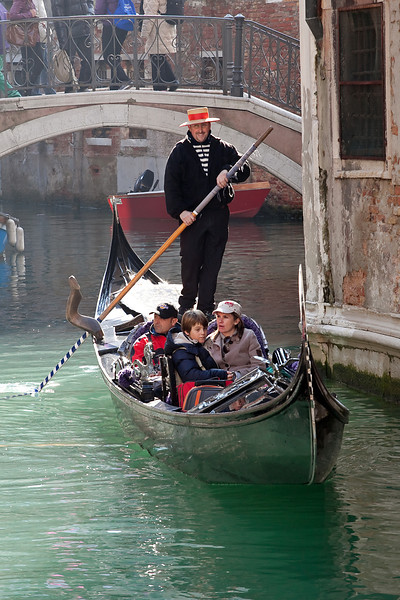 Gondola with tourists in channels, Venice, Italy