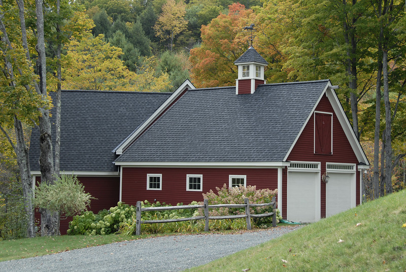 Typical red-painted Vermont house with Fall foliage turning color.