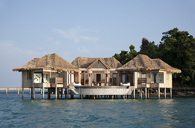Song Saa Private Island, Koh Ouen and Koh Bong, Cambodia  Number of Bungalows: 9  What's Unique: This new resort is the first to be built on Cambodia's mostly untouched islands in the Koh Rong archipelago. Song Saa spreads across two islands which are connected by a footbridge over a marine reserve, and with any luck you'll spot one of the protected sea turtles or seahorses during your stay. The resort's ultramodern overwater villas have an air of always-been-here authenticity thanks to the reclaimed wood from retired fishing boats and local driftwood incorporated into the architecture and furnishings. The organic design manages to effortlessly blend luxuries like private infinity-edge pools, outdoor showers, and twin bathtubs into the surrounding rainforest.  Over-the-Top Services: Indulge in a Buddhist-inspired treatment at the resort's rainforest wellness center or have local monks perform a traditional blessings ceremony for you. Staff can also turn your villa into a private cinema with a screen and projector for movie night.  Rates: From $1,415 per night.