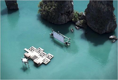 The Archipelago Cinema is certainly, the type of creation that you probably have to see for yourself to actually believe it exists.It is a floating cinema/MOVIE THEATRE on the rock riddled shoreline of Yao Noi, Thailand and was designed by German-born and Beijing-based architect Ole Scheeren for The Film on the rocks Yao Naoi Festival.  Guests are transported by boat to a glowing raft on the quiet waters of Kudu Island. They then view the screening from the raft that was built from recycled material. Watching a movie in an environment that has massive rocks, emerging from beneath the water, bodes well for a unique viewing experience.