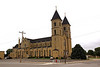 141 foot towers, 220 ft long, 110 ft wide at the transepts and 75 ft at the knave, the Romanesque church, in the form of a cross, faces west. St. Fidelis church and cemetery, Victoria, KS