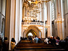 Vienna. Catholic Cathedral hosting visitors during music practice. The practice has a magnificent full string orchestra.