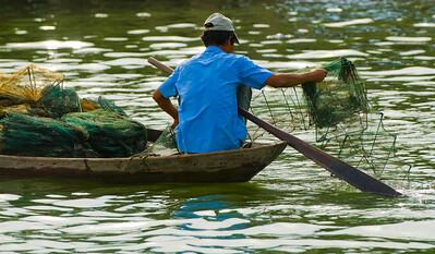 A Fisherman sets his nets on Thu Bon River - Hoi An - Vietnam