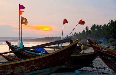Traditional fishing boats lined up on Mui Ne Beach at sunset, proudly fly their Vietnamese communsit flags.