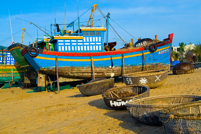 Traditional and more modern fishing boats wait ashore - Quy Nhon - Vietnam