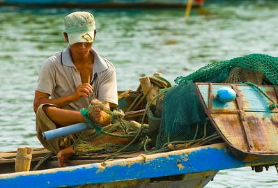 Fisherman repairing nets on Thu Bon River - Hoi An - Vietnam
