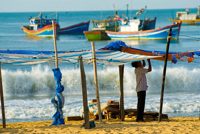 A man sets up shade for fish market whilst the fleet looks on - Quy Nhon - Vietnam