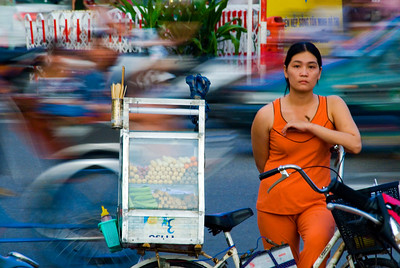 Street vendor leans on her bicycle ignoring the rushing traffic behind - Ho Chi Minh City (Saigon)