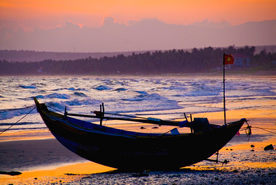 Fishing boat, flying a Vietnamese communist flag, on Mui Ne Beach at sunset.