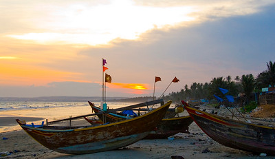 Traditional fishing boats lined up on Mui Ne Beach at sunset.