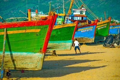 Boy plays amongst the beached fishing boats - Quy Nhon - Vietnam