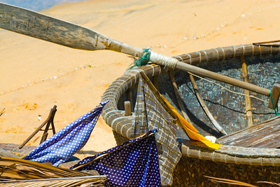 Traditional Vietnamese basket boat (thung chai) with colourful net bouy flags.