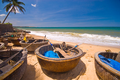 Traditional Vietnamese basket boats (thung chai) lined up by the sea on Mui Ne beach.