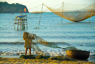 A fisherman brings his nets ashore for drying - Quy Nhon - Vietnam
