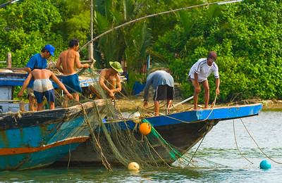 Fisherman sorting nets on Thu Bon River - Hoi An - Vietnam
