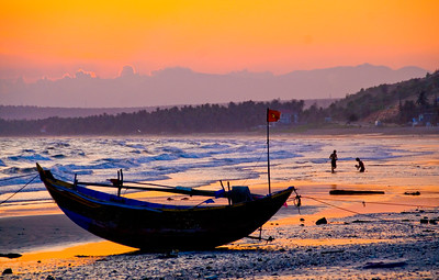 Traditional fishing boat flying a Vietnamese communist flag on Mui Ne beach at sunset.