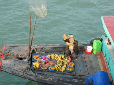 A woman sells fruit from her longtail.