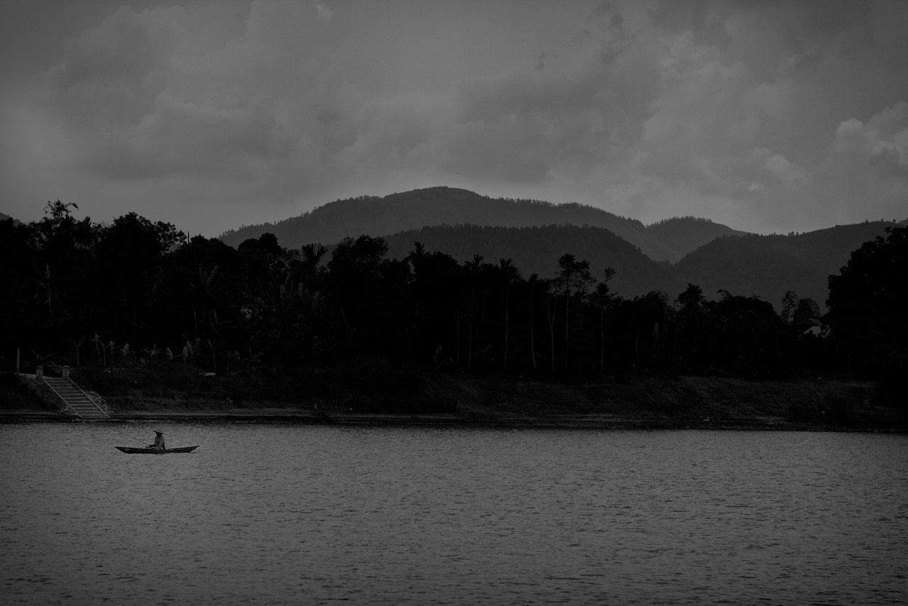 A woman fishing on the Perfume River, just outside of Hue.