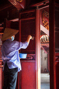 A woman washing some doors at the Temple of Literature.