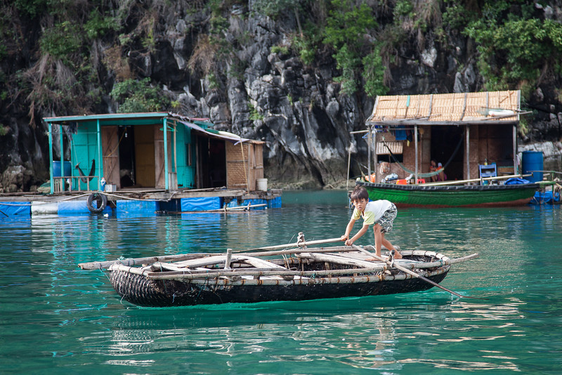 A small boy paddles around in a large fishing village.