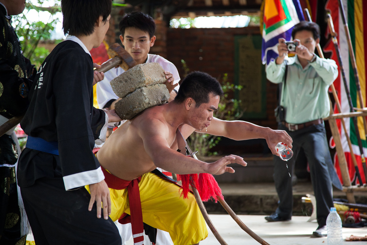 This guy put two sharpened spears to his throat, then thrust forward until the bamboo poles were bent. His classmates then loaded his back with concrete blocks and smashed them with hammers. Pretty impressive! The photographer in the back was there to feature the school in a newspaper, and he interviewed some of our group.