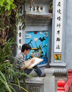 Art student in Hanoi sketching at the entrance to Ngoc Son Temple in Hoan Kiem Lake.