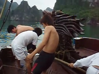 Vietnamese houseboat crew hauling anchor beside the flaming mane of the bow dragon.