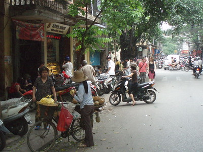 A bicycle-based vendor selling her fruit along the city streets of Hanoi.