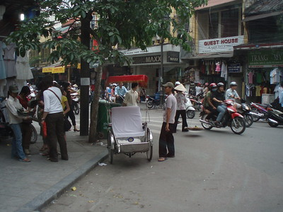 Rickshaw bicycle and scooters in Hanoi.
