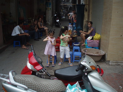 Children playing with bubbles on the sidewalk in Hanoi.