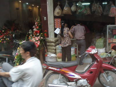 Sidewalk street vendors hawking their wares on the streets of Hanoi, using the front of their family home to establish a small business. Street-front property is highly valued in Vietnam, since most businesses are fun in this fashion.