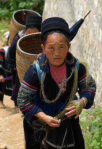 © Joseph Dougherty. All rights reserved.   H'mong woman hiking up the valley toward the Sa Pa market, multi-tasking by processing textile fibers by hand as she walks.