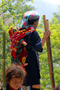 © Joseph Dougherty. All rights reserved.   Tay woman with child on her back and bamboo walking poles.