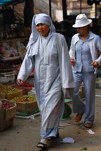 Vietnamese nun walking through the Sapa market.