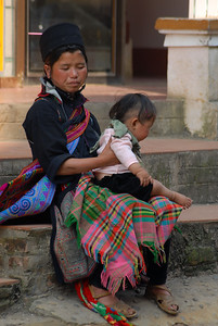 A Zai woman bounces her toddler on her lap.  The Zai commonly wear green and pink.